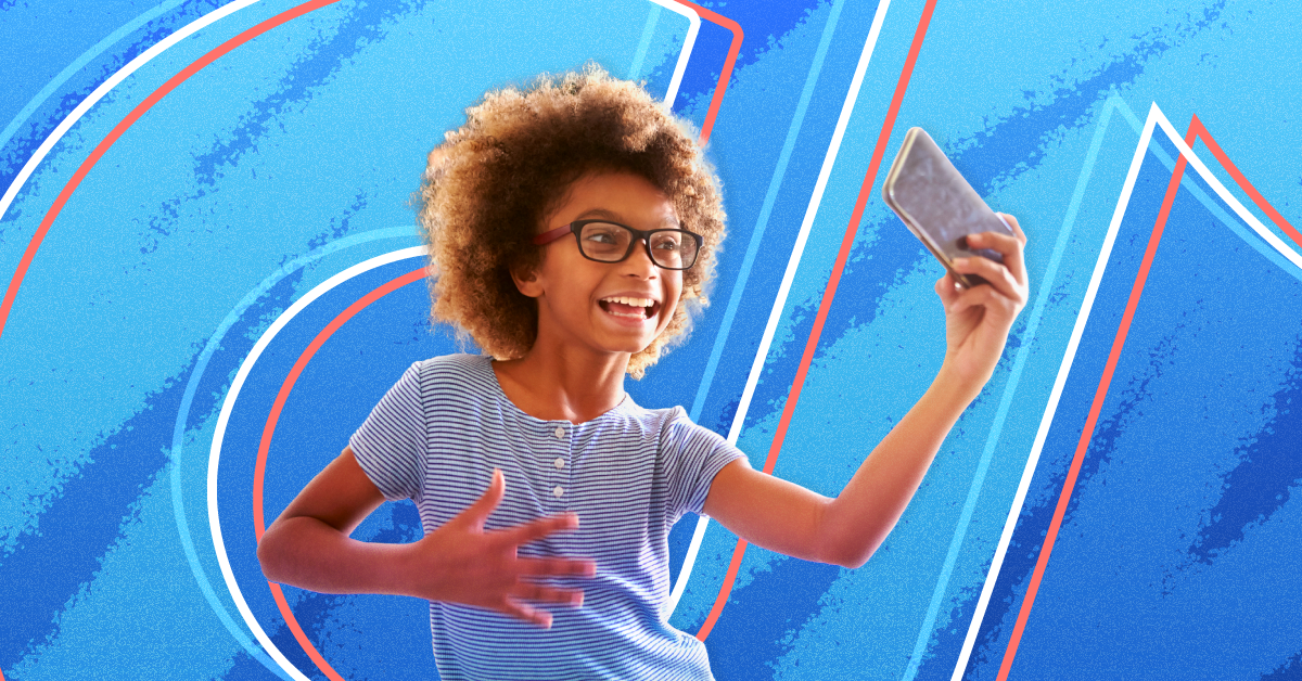 A young girl dances in front of her phone against an eggshell blue background with the TikTok logo on top